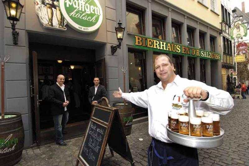 Köbes mit Kölsch-Kranz in der Hand vor dem Restaurant
